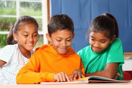 Photo pour Des jeunes enfants joyeux de l'école primaire lisant et apprenant ensemble en classe - image libre de droit