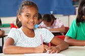 Schoolgirl in classroom writing