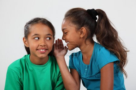 Two girls keeping a secret