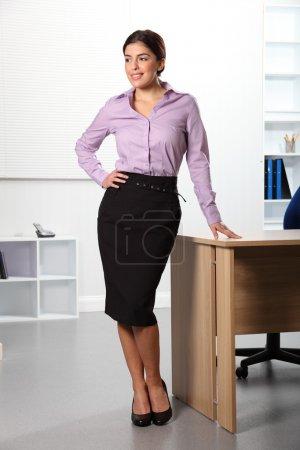 Photo pour Belle jeune femme d'affaires confiante debout dans le bureau à côté de son bureau, regardant loin avec un sourire . - image libre de droit