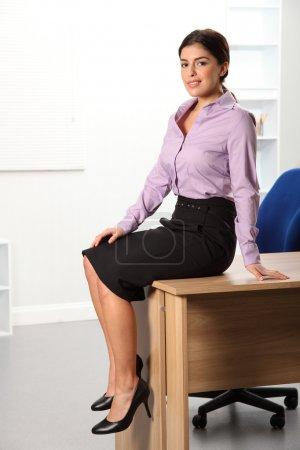 Photo pour Belle jeune femme d'affaires dans le bureau assis sur son bureau . - image libre de droit