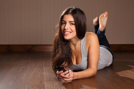 Photo for Beautiful young smiling woman using smart phone to listen to music while relaxing at home lying on the floor. - Royalty Free Image