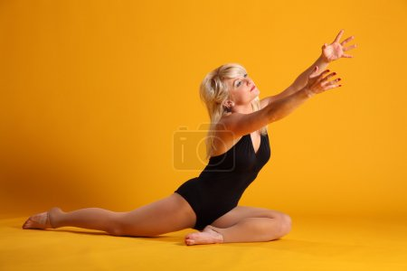 Blonde girl on yellow reaching out