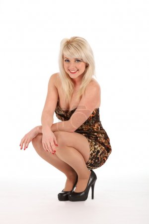 Sexy blonde crouches in dress