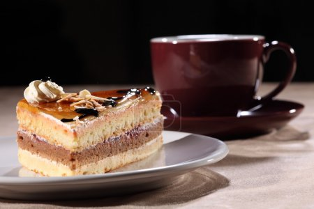 Photo for Tasty slice of layered coffee cake on a white plate, along with cherry black coffee cup and saucer. Cake topped with syrup, chocolate sauce and whipped cream - Royalty Free Image