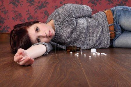 Teenager overdose on pills lying on floor
