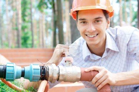 Photo pour Proximité place portrait d'un jeune travailleur souriant réparer un tuyau à l'extérieur avec espace copie - image libre de droit