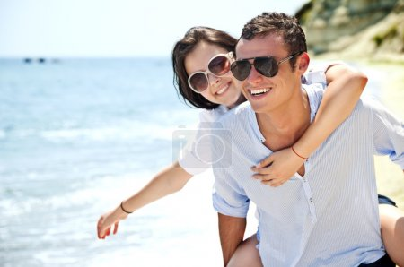 Piggyback ride to beautiful female on solitary beach, happy couple
