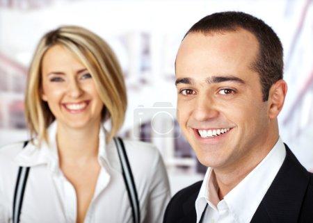 Photo pour Couple d'affaires souriant regardant caméra mâle sur la mise au point - image libre de droit