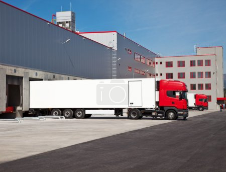 Photo for Cargo trucks at an entrance of a warehouse - Royalty Free Image