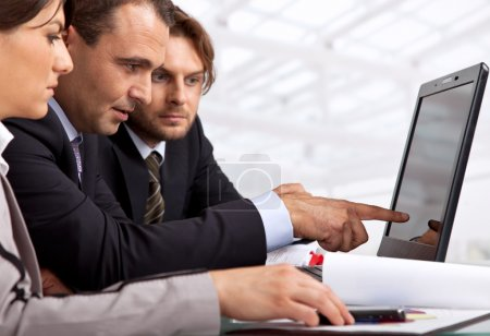 Photo for Three businesspeople sitting by a laptop male is pointing at it - Royalty Free Image