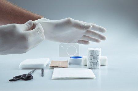 Photo pour Fournitures médicales de premiers soins et un médecin portant des gants de protection - image libre de droit