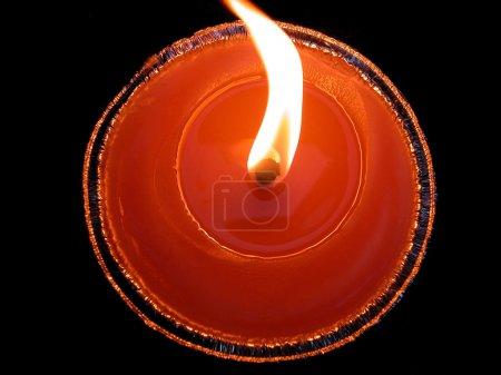 Photo pour Gros plan d'une bougie rouge circulaire sur fond noir - image libre de droit