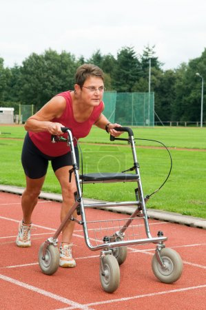 Photo for Disabled athlete at the starting line with her walker. Caricature picture to illustrate disability, ability, getting older, not wanna quit. - Royalty Free Image