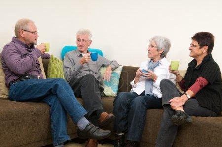 Foto de Grupo de cuatro personas mayores tomando café, charlando y tomando una gran famili juntos. - Imagen libre de derechos