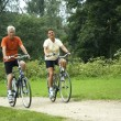 Active senior couple biking in the park....