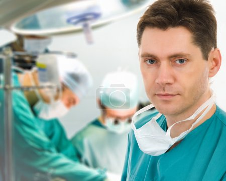 Photo pour Chirurgien avec deux médecins en salle d'opération - image libre de droit