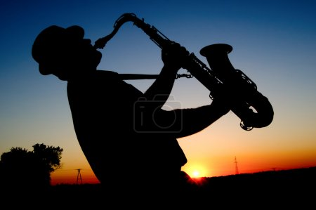 Photo for Outline saxophonist on the background of the sun in the hot summer afternoons - Royalty Free Image