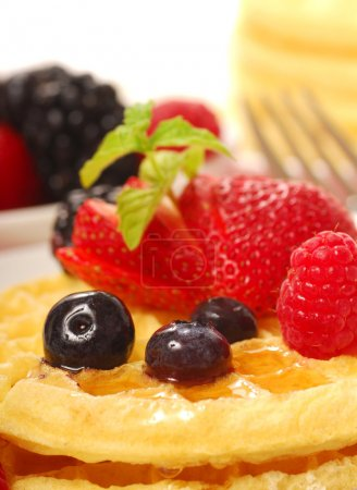 Photo for Freshly made waffles with a variety of fruit and maple syrup - Royalty Free Image