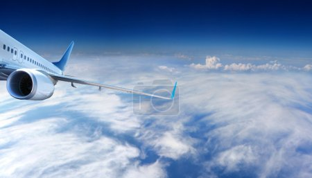 Photo for Big jet plane flying in cloudy sky - Royalty Free Image