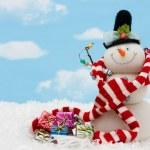 Snowman wearing scarf on blue sky background, merr...