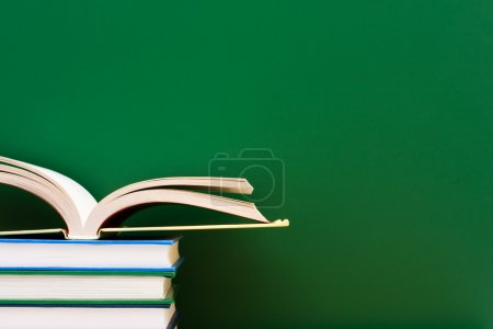 Photo for Stack of books one open in front of the chalkboard, School Days - Royalty Free Image