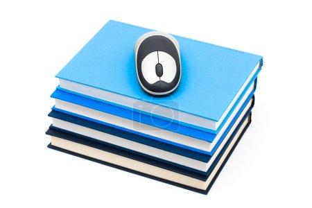 Photo pour Une pile de livres bleus avec une souris sans fil sur le dessus, Étude en ligne - image libre de droit