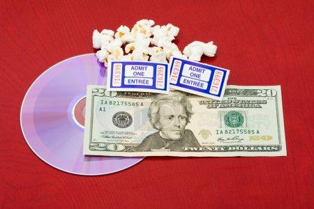 Photo pour Quelques grains de pop-corn avec un DVD et des billets sur un fond de bois, film et pop-corn - image libre de droit