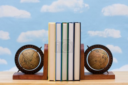 A stack of book between book end with a sky backgr...