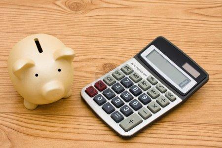 Photo pour Une tirelire et une calculatrice assis sur un fond en bois, Calcul de vos dépenses - image libre de droit