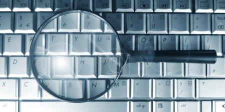 Foto de Concepto de búsqueda con teclado portátil y lupa - Imagen libre de derechos