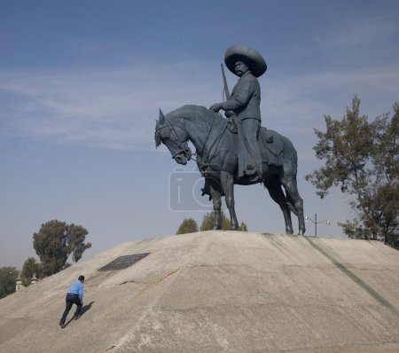 Photo pour Immense statue d'emiliano zapata, héros révolutionnaire, le cheval toluca Mexique. homme grimpant sur la statue montre taille relative - image libre de droit