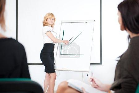 Photo pour Jeune femme d'affaires faisant une présentation pour son équipe - image libre de droit