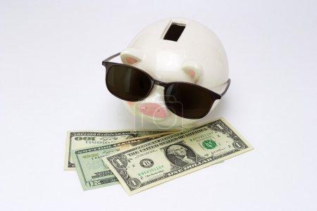 Photo pour Image conceptuelle de tirelire portant des lunettes de soleil manquant sur les dollars américains - image libre de droit