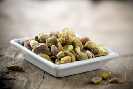 Small bowl of pistachios on wooden table