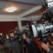 Videocamera and journalists at press conference...