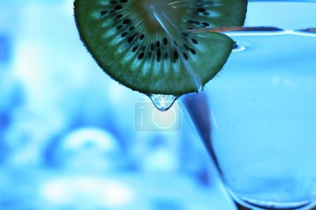 Photo for Glass with a plate kiwi on a dark blue background - Royalty Free Image