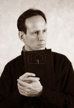 Photo pour Pensé l'homme avec la bible sur un fond léger - image libre de droit