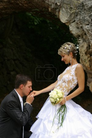 Photo for The groom kisses a hand to the bride kneeling - Royalty Free Image