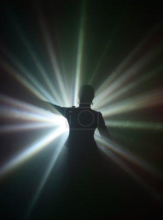 Photo pour Silhouette de danseuse dans les rayons de lumière - image libre de droit