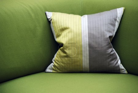 Photo for Green sofa with a striped pillow - Royalty Free Image