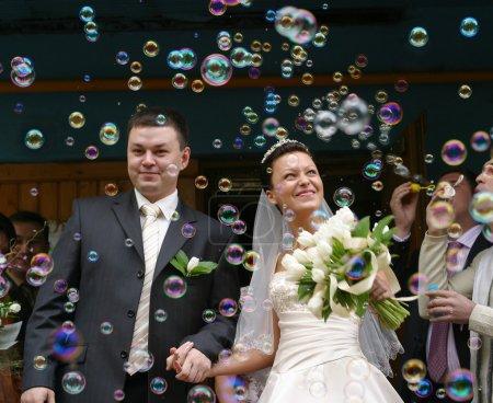 Photo pour Heureux couple nouvellement marié sur fond de bulles de savon - image libre de droit