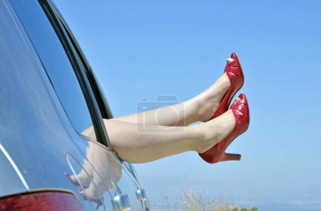 Woman with red shoes by the way the car window on vacation. Concept of happ