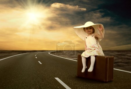 Photo for Little girl waiting on the road with her vintage baggage - Royalty Free Image