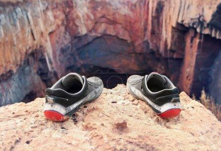 Foto de Zapatos viejos cutre del suicidio al borde de un precipicio - Imagen libre de derechos