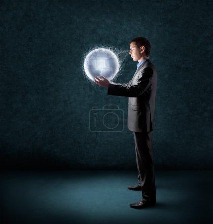 Photo pour Homme d'affaires tenant planète Terre rayonnante - image libre de droit