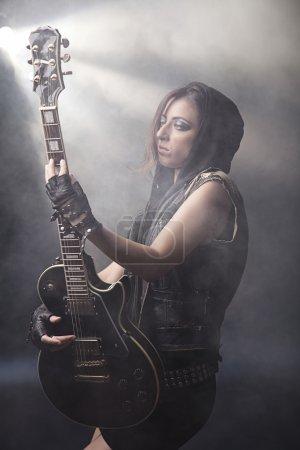 Photo pour Une fille belle rockstar posant avec sa guitare électrique. dans l'ensemble une alternative punk rock regarde avec une expression forte, dans le style avec beaucoup d'adolescents ces - image libre de droit
