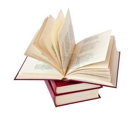 Photo pour Empilement de livres dans une couverture en cuir rouge avec lettrage or avec un livre ouvert - image libre de droit