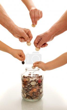 Photo pour Mains de différentes générations mettre des pièces dans un bocal en verre concept d'éducation financière - image libre de droit