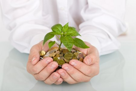Photo for Business man holding young plant rising from a pile of coins - good investment and savings concept - Royalty Free Image